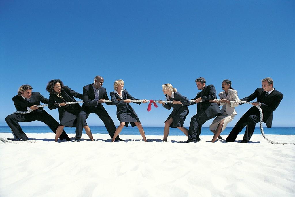 Hommes et femmes d'affaire en compétition sur la plage